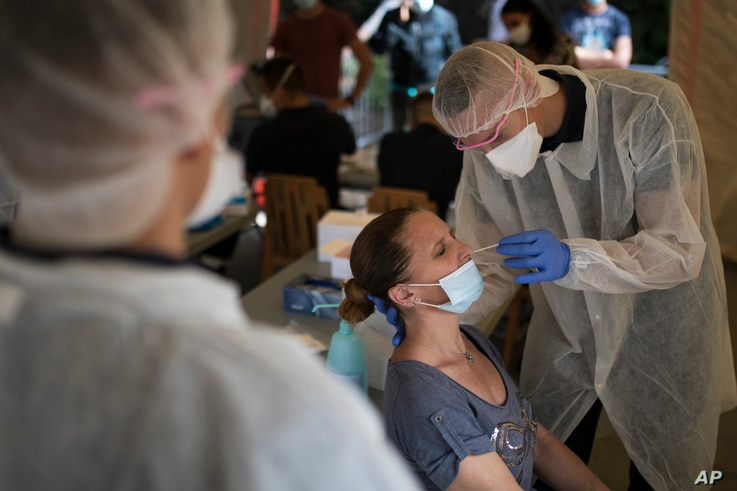 A woman is tested for COVID-19 at a mobile testing center in Marseille, France, Sept. 24, 2020.