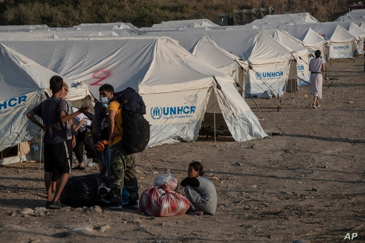 Migrants arrive at a temporary camp near Mytilene town, on the northeastern island of Lesbos, Greece, Sept. 12, 2020.
