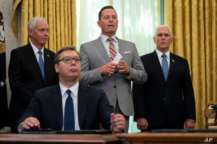 President Donald Trump's special envoy on Serbia and Kosovo Richard Grenell speaks during a signing ceremony with Serbian President Aleksandar Vucic sitting at a desk in the Oval Office of the White House in Washington, Sept. 4, 2020.
