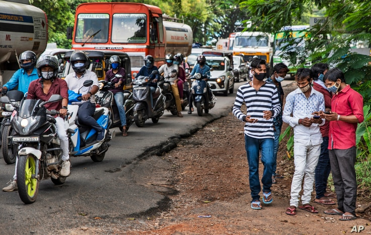 Commuters wearing masks wait at a traffic intersection in Kochi, Kerala state, India, Sept.28, 2020.