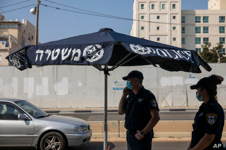 Israeli police officers wearing face masks to protect against coronavirus secure a check point on the first day of three-week lockdown in Bnei Brak, Israel, Sept 18, 2020.