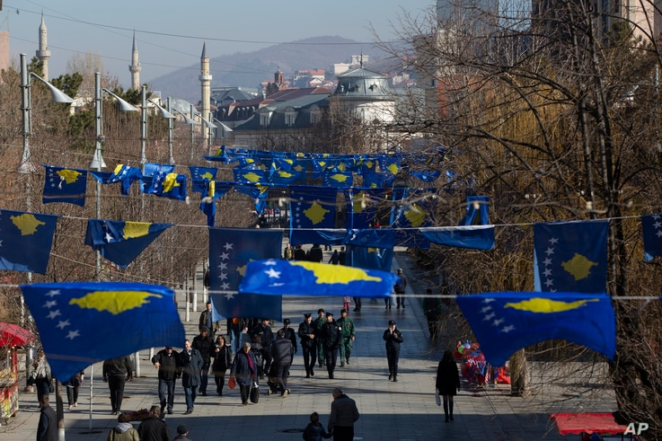 FILE - Kosovo's flags decorate a street as people walk during its 12th independence anniversary, in the capital Pristina, Feb. 17, 2020.