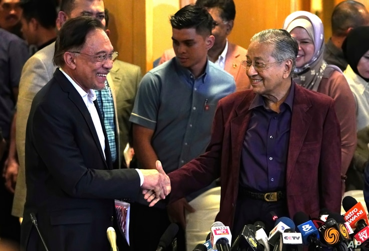 FILE - Malaysian Prime Minister Mahathir Mohamad shakes hand with successor Anwar Ibrahim in Putrajaya, Feb. 22, 2020.