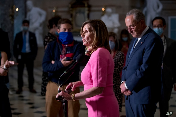 FILE - House Speaker Nancy Pelosi, center, accompanied by Senate Minority Leader Sen. Chuck Schumer, right, speaks to reporters on Capitol Hill in Washington, Aug. 7, 2020.