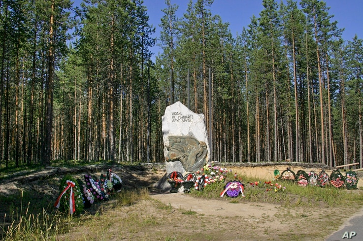 "A giant stone marking the site, known as Sandramokh engraved with the words ""People Don't Kill Each Other"" at a mass grave where thousands of victims of Stalin's Great Terror were executed, outside Medvezhyegorsk, Russia, Aug. 9, 2006."