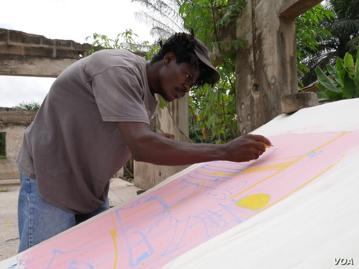 Sel Kofiga paints a piece of fabric he bought at Kantamanto market, in Accra, Ghana, Sept. 22, 2020. (Stacey Knott/VOA)