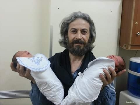 Foad Ahmed el-Mohamed, was a local journalist in Deir el-Zour. Here holding a twin born in the hospital he used to work at in 2014.