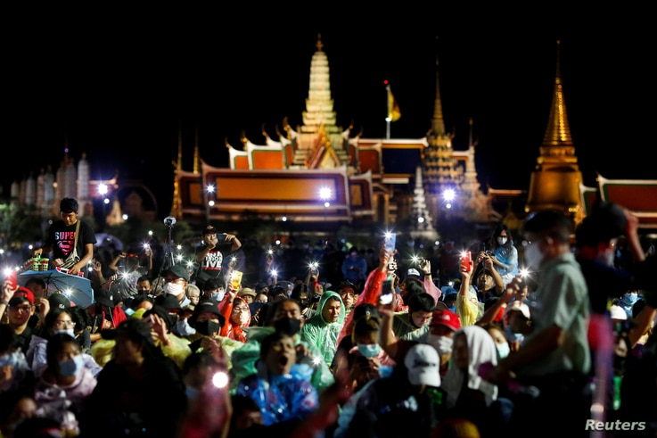 Pro-democracy protesters light up their mobile phones as they attend a mass rally to call for the ouster of Prime Minister Prayuth Chan-ocha's government and reforms in the monarchy, in Bangkok, Thailand, Sept. 19, 2020.