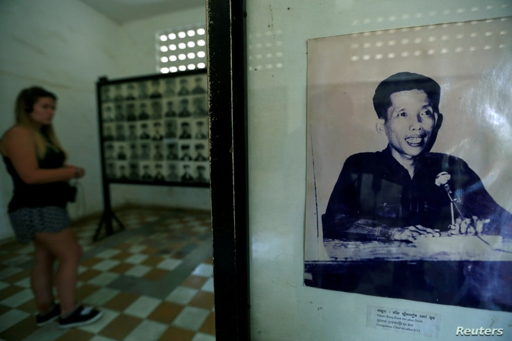 FILE - A visitor walks past a picture of Kaing Guek Eav, alias
