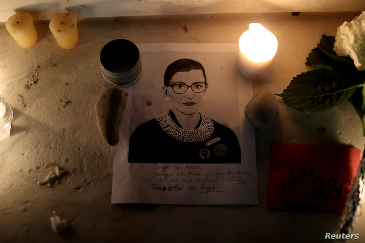 Candles and an image of late U.S. Supreme Court Justice Ruth Bader Ginsburg are seen as people gather in front of the U.S. Supreme Court following her death, in Washington, Sept. 19, 2020.