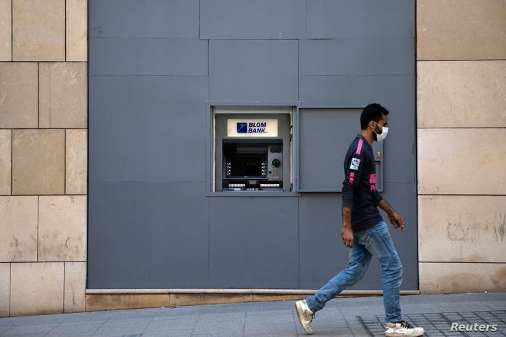 FILE - A man wearing a face mask walks past a fortified Blom Bank ATM machine, in Beirut, Lebanon, Aug. 21, 2020.