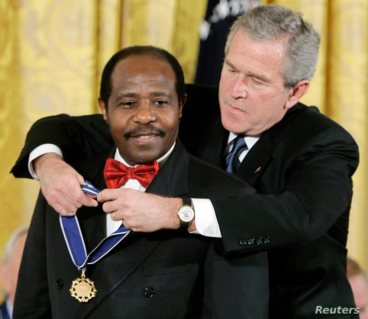 FILE - U.S. President George W. Bush presents a Presidential Medal of Freedom to Paul Rusesabagina, who sheltered people at a hotel he managed during the 1994 Rwandan genocide, at a ceremony at the White House in Washington, Nov. 9, 2005.