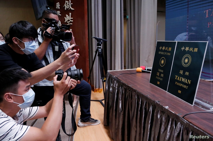 Members of the media take photos of paper cut-outs of the old and new (R) Taiwan passport displayed in Taipei, Taiwan, Sept. 2, 2020.