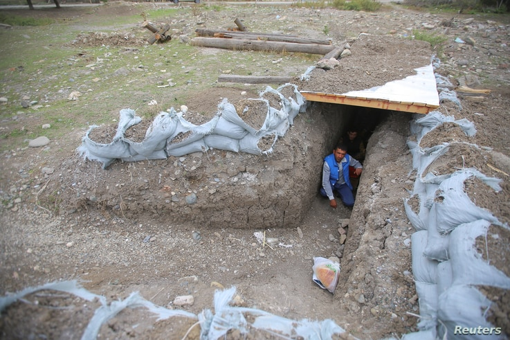 Local residents take shelter in a dugout during the fighting over the breakaway region of Nagorno-Karabakh in the city of Terter, Azerbaijan, Sept. 30, 2020.
