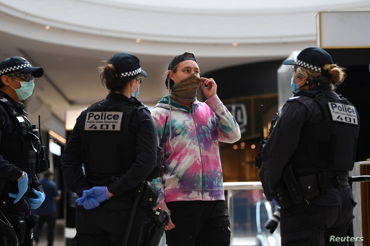 Victoria Police officers speak with a masked member of the public in a shopping center following an anti-lockdown protest in response to the city's COVID-19 restrictions in Melbourne, Australia, Sept. 20, 2020.