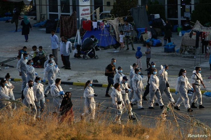 Greek officials wearing personal protective equipment arrive in an area where refugees and migrants from the destroyed Moria camp are sheltered on the island of Lesbos, Sept. 18, 2020.