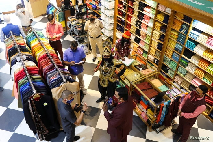 A volunteer of District Magistrate (DM) office dressed as Yamraj, or Hindu God of death, and Civil Defense officers fine people for not wearing masks inside a shop in New Delhi, India, Sept. 28, 2020.