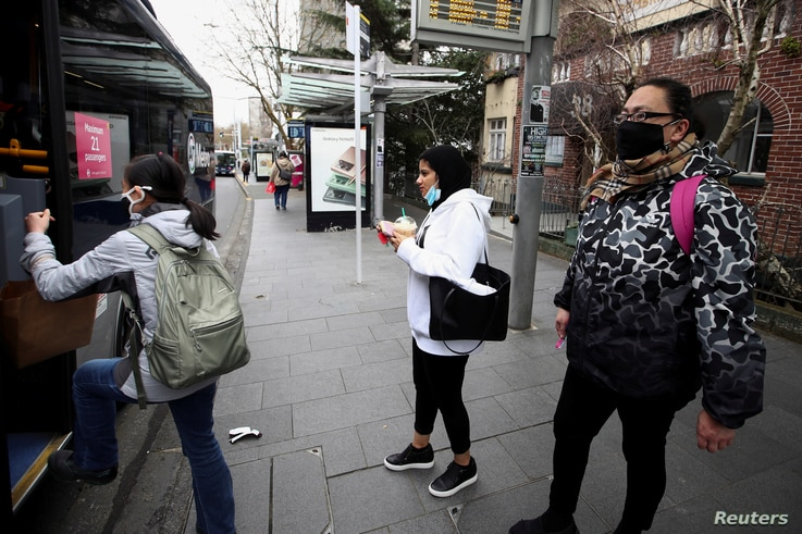 People wearing face masks prepare to board a bus on the first day of New Zealand's new coronavirus disease safety measure that mandates wearing of a mask on public transport, in Auckland, August 31, 2020.