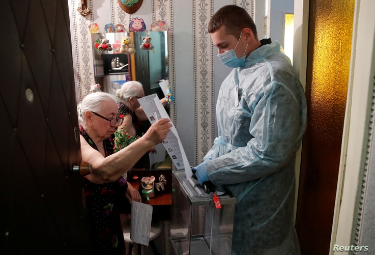 An elderly woman casts a ballot during municipal elections in Tomsk, Russia, Sept. 13, 2020.
