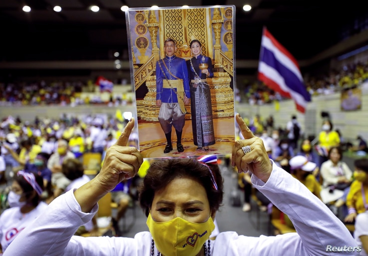"A member of Thai right-wing group ""Thai Pakdee"" (Loyal Thai) holds a picture of King Maha Vajiralongkorn with Queen Suthida attend a rally in support of the government and the monarchy, in Bangkok, Thailand, Aug. 30, 2020."