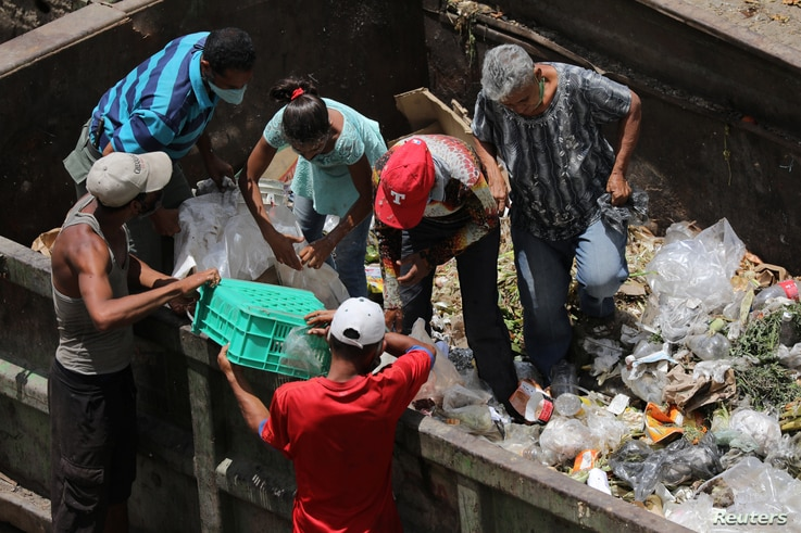 People search for food in a dumpster during the closing hour of the Coche wholesale market during the COVID-19 outbreak in Caracas, Venezuela on July 31, 2020.