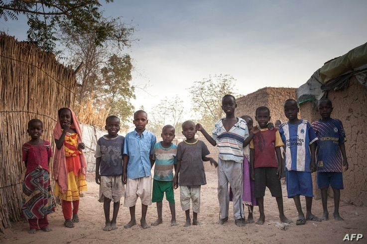 Sudanese refugees children pose for photographs, in the Treguine camp, in Hadjer Hadid, in the Ouaddaï region of eastern Chad,…