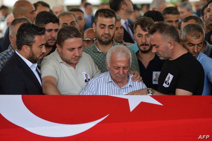 Relatives of Osman Kose, a 38-year-old Turkish diplomat killed in Iraq, mourne in front of the coffin covered with a Turkish…