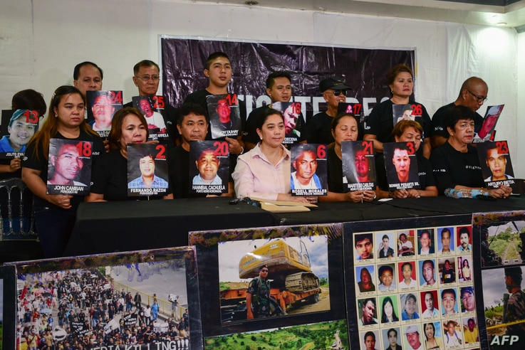Relatives and supporters of victims of the 2009 Maguindanao massacre hold pictures of the victims during a press conference…