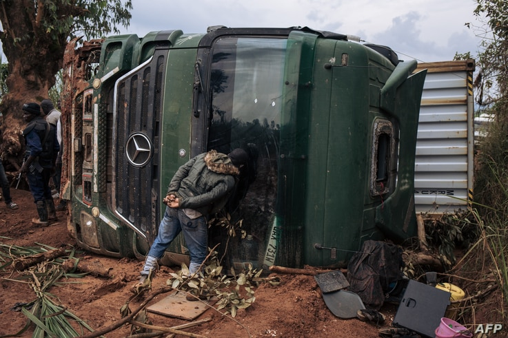 A passer-by looks inside an overturned truck in the middle of National Road 27 in Ituri Province, northeastern Democratic…