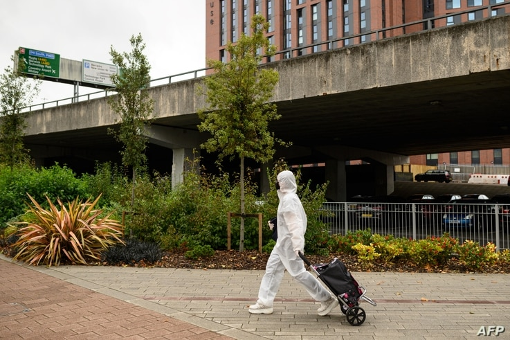 A student wearing full-body PPE due to the COVID-19 pandemic, walks towards the Coventry University Library at the beginning of…