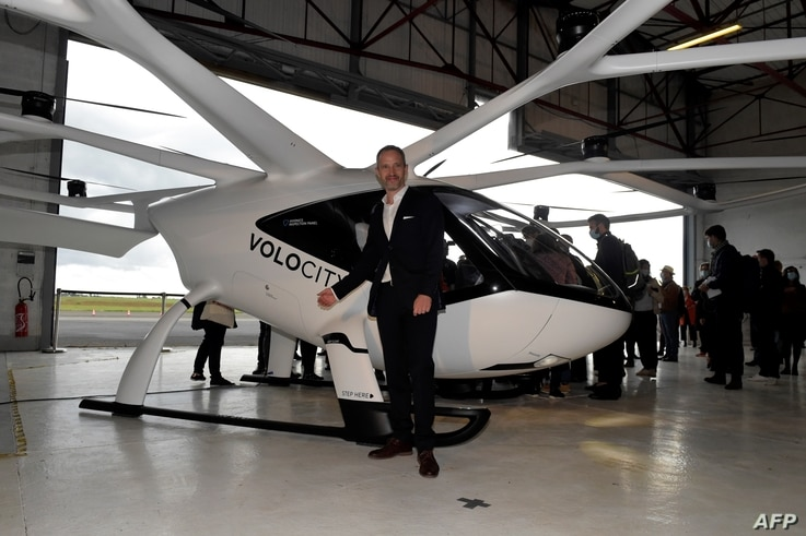 Florian Reuter, CEO of German start-up Volocopter GmbH poses in front of  a Volocopter unmanned air taxi transport presented at the Pontoise airport in Cormeilles-en-Vexin on Sept. 30, 2020 as part of the launch of the  urban air mobility industry branch.
