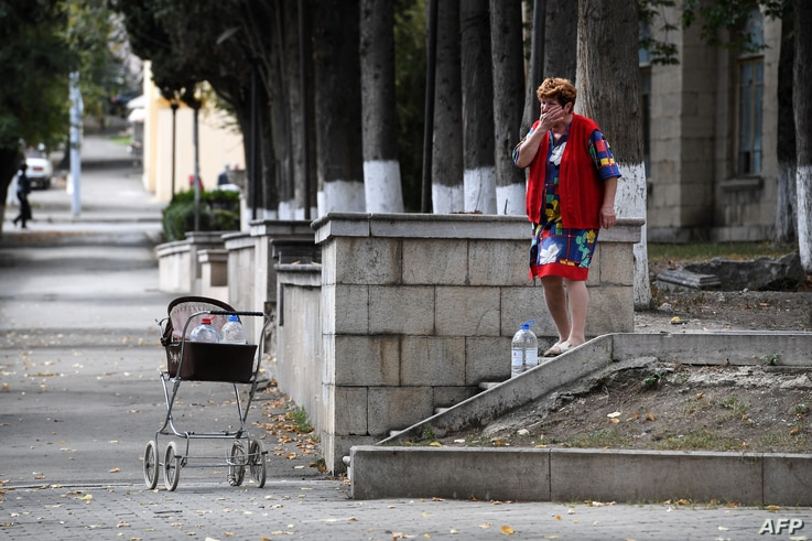 A woman collects drinking water from a spring on a street in the breakaway Nagorny Karabakh's main city of Stepanakert on…