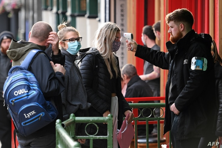 A security guard uses a handheld thermometer to take the temperature of customers, wearing face masks or coverings due to the…