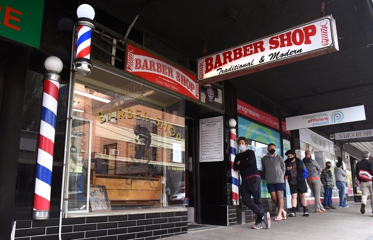 Men queue for a haircut outside a barber shop in Melbourne on October 19, 2020, as some of the city's three-month-old stay-at…