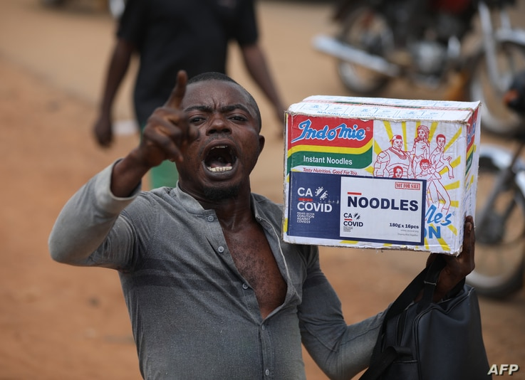 A man reacts while carrying a bag of noodles during a mass looting of a warehouse that have COVID-19 food palliatives that were…