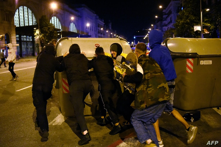 A group of people push a dustbin after a demonstration against curfew and deprivation of rights, in Barcelona, on October 26,…