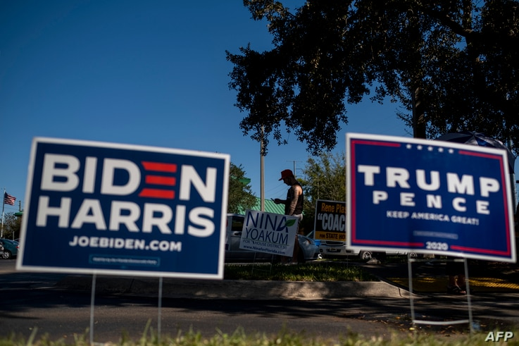 Biden and Trump campaign signs are displayed as voters line-up to cast their ballots during early voting at the Alafaya Branch…