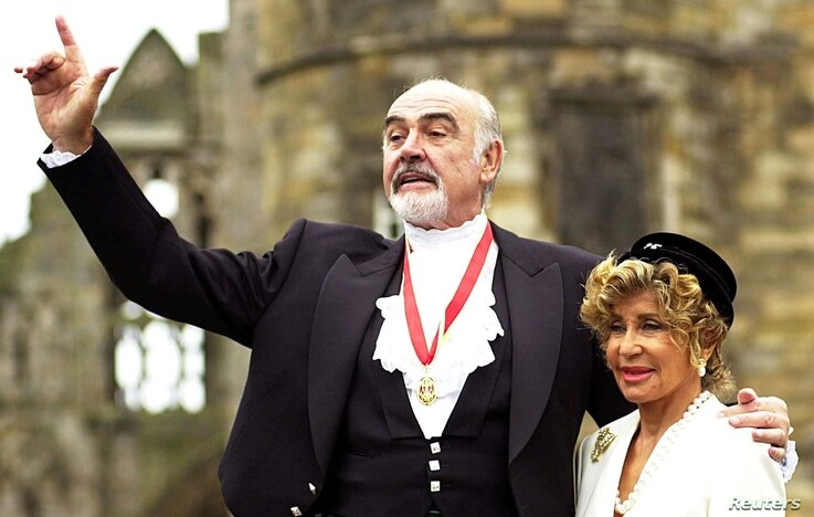 Sir Sean Connery, with wife Micheline (R), pose for photographers after he was formally knighted by the Britain's [Queen…