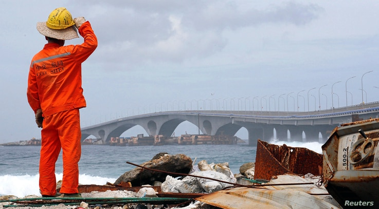A construction worker looks on as the China-funded Sinamale bridge is seen in Male, Maldives September 18, 2018. REUTERS/Ashwa…