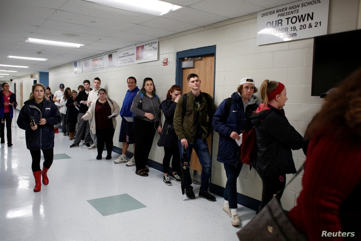 FILE - New voters, including many University of New Hampshire students, stand in line to fill out voter registration forms in Durham, New Hampshire, Nov. 6, 2018.