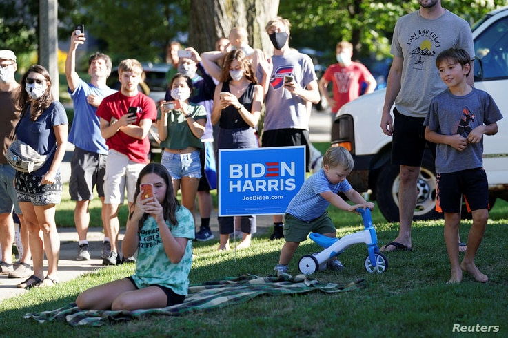 Local residents snap pictures and look on as Democratic U.S. presidential nominee and former Vice President Joe Biden…
