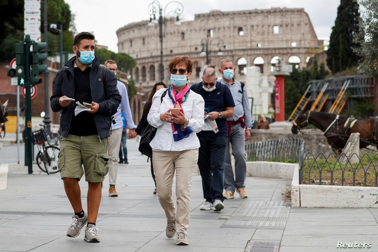 People wear face masks as local authorities in the Italian capital Rome order face coverings to be worn at all times out of…