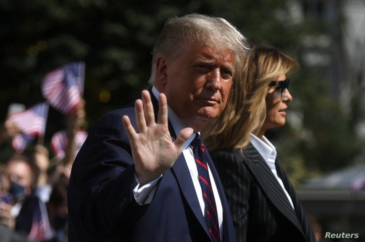 U.S. President Donald Trump waves to reporters as he departs with first lady Melania Trump for campaign travel.