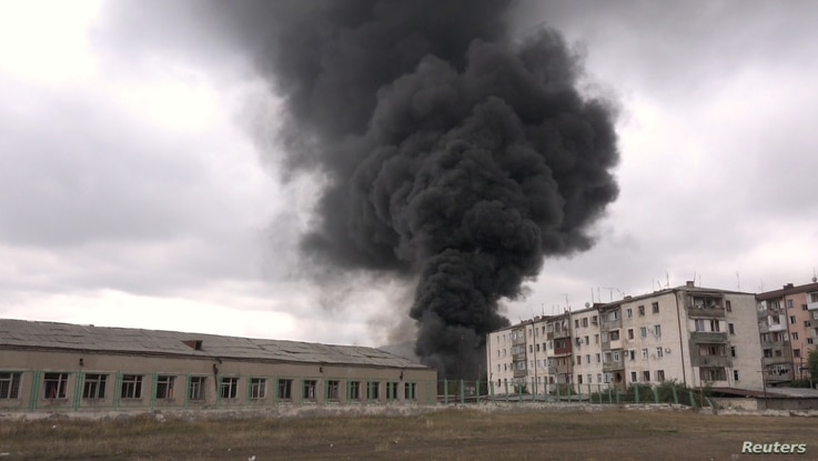 Black smoke rises near buildings during a military conflict over the breakaway region of Nagorno-Karabakh, in Stepanakert, Oct, 4, 2020 in this still image taken from video obtained on October 6, 2020.