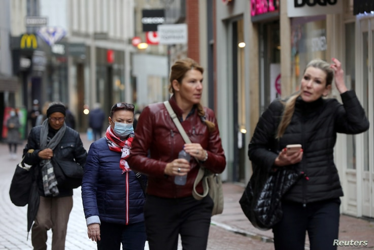 People with and without protective masks walk through the shopping street as the spread of coronavirus disease (COVID-19)…