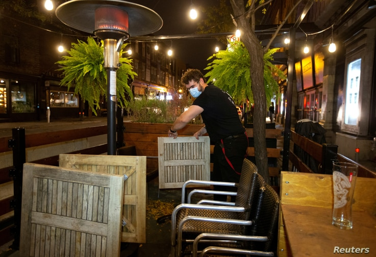 FILE PHOTO: An employee dismantles the terrasse at closing time as the Quebec government has ordered all restaurants, bars and…