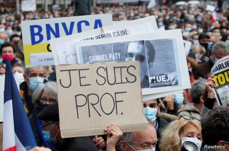 People gather at the Place de la Republique in Paris, to pay tribute to Samuel Paty, the French teacher who was beheaded on the…