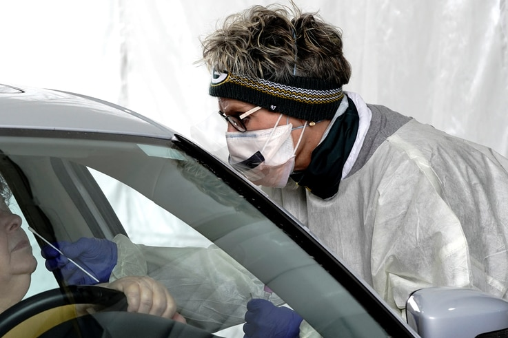 FILE PHOTO: Registered nurse (RN) Tammy Fellenz, wearing an NFL Green Bay Packers headband, takes a patient's nasal swab at a…