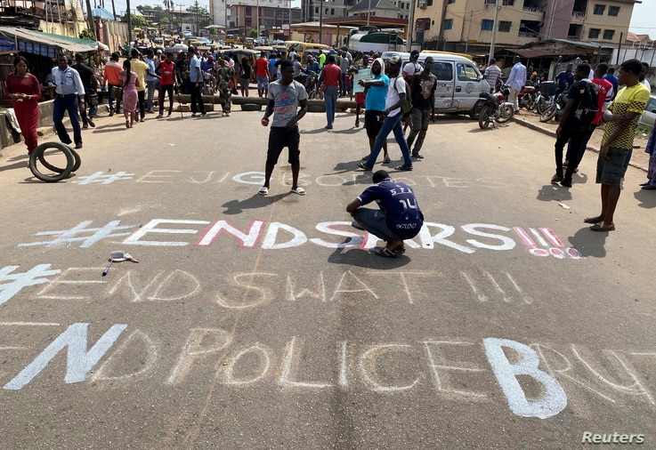 A demonstrator paints 'End Sars', referring to the Special Anti-Robbery Squad police unit, on a street during a protest.