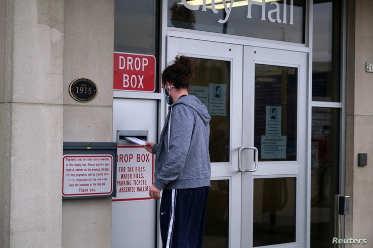 A person drops off their absentee ballot at a drop box at City Hall as early voting for the upcoming presidential election…